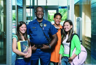 Security officer posing with teenagers