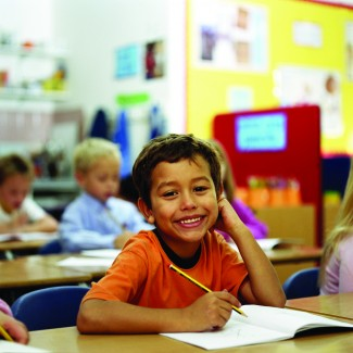 Children (6-8) sitting at desks in classroom, focus on boy writing