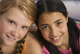 Two smiling preteen girls